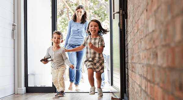 A mother and two children joyfully entering their home stock photo